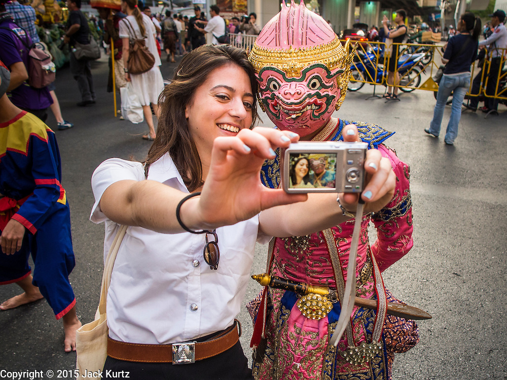 "14 JANUARY 2015 - BANGKOK, THAILAND:  An exchange student takes a ""selfie"" of herself and a soldier in the Thai monkey army, a popular character from Thai mythology, during the 2015 Discover Thainess parade. The Tourism Authority of Thailand (TAT) sponsored the opening ceremony of the ""2015 Discover Thainess"" Campaign with a 3.5-kilometre parade through central Bangkok. The parade featured cultural shows from several parts of Thailand. Part of the ""2015 Discover Thainess"" campaign is a showcase of Thailand's culture and natural heritage and is divided into five categories that match the major regions of Thailand – Central Region, North, Northeast, East and South.    PHOTO BY JACK KURTZ"