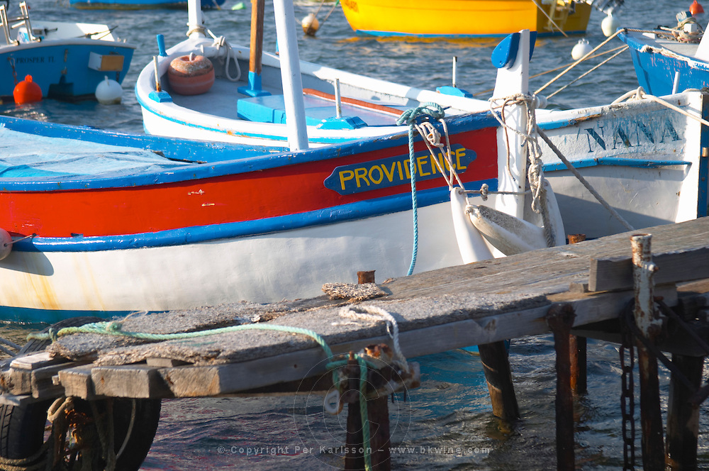 Typical Provencal fishing boats painted in bright colours white, blue, green red yellow, moored at a jetty Le Brusc Six Fours Var Cote d'Azur France