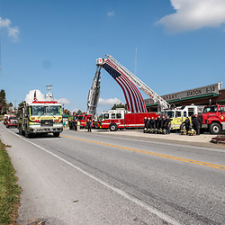 Peach Bottom, PA, USA - October 30, 2014: Fellow firefighters salute the funeral procession for a fallen volunteer firefighter in Lancaster County.