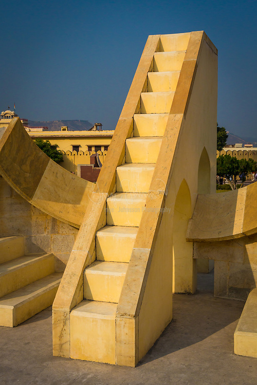 "The Jantar Mantar is a collection of architectural astronomical instruments, built by Sawai Jai Singh who was a Rajput king served Emperor Aurangzeb and later Mughals. The title of (King) and Sawai was bestowed on him by Emperor Mohammad Shah. Jai Singh II of Amber built his new capital of Jaipur between 1727 and 1734. It is also located in Ujjain and Mathura. It is modeled after the one that he had built at the Mughal capital of Delhi. He had constructed a total of five such facilities at different locations, including the ones at Delhi and Jaipur. The Jaipur observatory is the largest and best preserved of these. It has been inscribed on the World Heritage List as ""an expression of the astronomical skills and cosmological concepts of the court of a scholarly prince at the end of the Mughal period"". Early restoration work was undertaken under the supervision of Major Arthur Garrett, a keen amateur astronomer, during his appointment as Assistant State Engineer for the Jaipur District. The jantar mantar was made by sawai jai singh as he was particularly interested in learning about the sky above his head. The observatory consists of fourteen major geometric devices for measuring time, predicting eclipses, tracking stars' location as the earth orbits around the sun, ascertaining the declinations of planets, and determining the celestial altitudes and related ephemerides. Each is a fixed and 'focused' tool. The Samrat Yantra, the largest instrument, is 90 feet (27 m) high, its shadow carefully plotted to tell the time of day. Its face is angled at 27 degrees, the latitude of Jaipur. The Hindu chhatri (small cupola) on top is used as a platform for announcing eclipses and the arrival of monsoons.<br /> Built from local stone and marble, each instrument carries an astronomical scale, generally marked on the marble inner lining. Bronze tablets, all extraordinarily accurate, were also employed. Thoroughly restored in 1901, the Jantar Mantar was declared a national monument in 19"