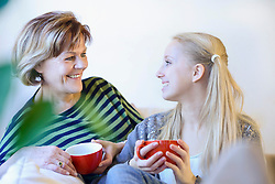 Grandmother and granddaughter in conversion on couch