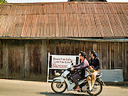 "13 MARCH 2016 - LUANG PRABANG, LAOS:  Lao people ride a motorcycle past a home for sale in Luang Prabang. The for sale sign being in English indicates who the property is being marketed to. Luang Prabang was named a UNESCO World Heritage Site in 1995. The move saved the city's colonial architecture but the explosion of mass tourism has taken a toll on the city's soul. According to one recent study, a small plot of land that sold for $8,000 three years ago now goes for $120,000. Many longtime residents are selling their homes and moving to small developments around the city. The old homes are then converted to guesthouses, restaurants and spas. The city is famous for the morning ""tak bat,"" or monks' morning alms rounds. Every morning hundreds of Buddhist monks come out before dawn and walk in a silent procession through the city accepting alms from residents. Now, most of the people presenting alms to the monks are tourists, since so many Lao people have moved outside of the city center. About 50,000 people are thought to live in the Luang Prabang area, the city received more than 530,000 tourists in 2014.   PHOTO BY JACK KURTZ"