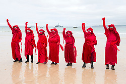 © Licensed to London News Pictures; 11/06/2021; St Ives, Cornwall UK. G7 summit in Cornwall. XR's Red People protest with HMS Tamar in the background at a protest by Extinction Rebellion in St Ives on the first day of the G7 summit. Photo credit: Simon Chapman/LNP.