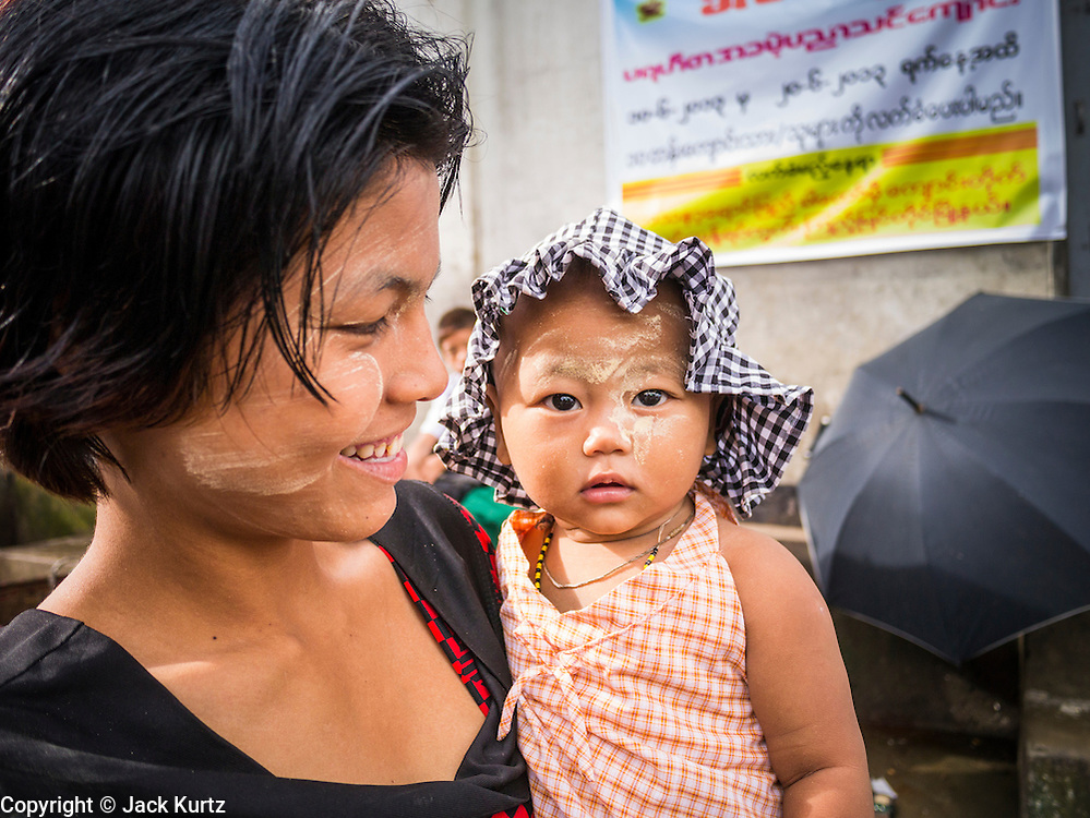 13 JUNE 2013 - YANGON, MYANMAR:  A woman and her child wait for a boat on the Irrawaddy River at the Aung Mingalar Jetty in Yangon. The jetty is a stop for commuters who live on the far side of the Irrawaddy River and ride small boats back and forth across the river. Yangon, formerly Rangoon, is Myanmar's commercial capital and used to be the national capital. The city is on the Irrawaddy River and has a vibrant riverfront.   PHOTO BY JACK KURTZ