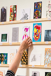 © Licensed to London News Pictures. 08/04/2016. A member of staff make final preperations for the The Royal College of Arts(RCA) 22nd annual Stewarts Law RCA Secret exhibition of postcards designed by well-known artists and designers. London, UK. Photo credit: Ray Tang/LNP