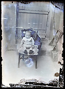 eroding glass plate photo of a toddler sitting on a chair