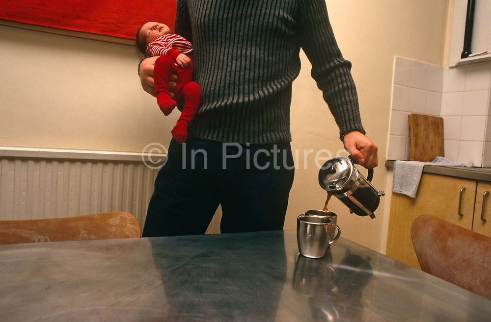 An unidentified father in the act of pouring coffee from a cafetiere into two metallic silver mugs in while holding his sleeping baby son in his London kitchen. The unconscious child is a few months old and the parent stands expertly holding both hot liquid and infant as if juggling pleasure and parenthood simultaneously. The sleeping child is limp in the father's arm and is dressed in the same scarlet red as the vibrant colour on the wall behind. We only see the man's upper-legs and torso but the baby is tiny against his body making the scale of both young and old. otherwise, the generic room is bare of decoration or possessions - only a drying cloth and chopping board is seen on the draining board, near plain white tiles.