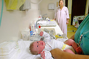 Nurses dresses a newborn infant baby in a maternity ward while the mother watches
