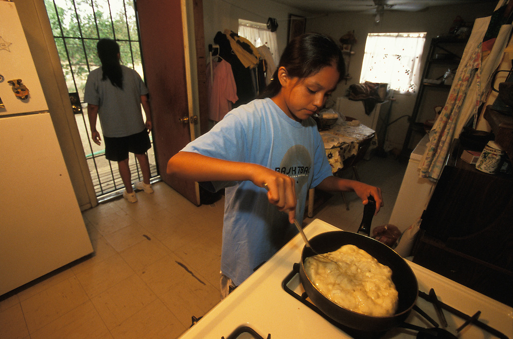 An Apache girl learns how to make corn bread as part of the preparation for her Sunrise Dance, a first menstruation rite, on the San Carlos Apache Indian Reservation in Arizona, USA. June 2004. Her mother looks out through the kitchen door. The Sunrise Dance is the most important ceremony of the Apache Indians. It is held during the summer, within one year after the girl has had her first menstruation, and lasts for four days. The ceremony is an enactment of the Apache creation myth and during the rites the girl 'becomes' Changing Woman, a mythical female figure, and comes into possession of her healing powers. The rites are also supposed to prepare the girl for adulthood and to give her a long and healthy life without material wants.