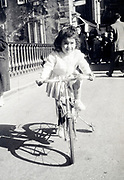 girl riding a bicycle with extra wheel support France 1958