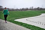 Nederland, Deest, 11-2-2020 In de rivier de Waal is het verhoogd water. Het rivierwater is de uiterwaarden ingelopen en staat tot aan de voet van de dijk . Een vrouw loopt op de dijk .Foto: Flip Franssen