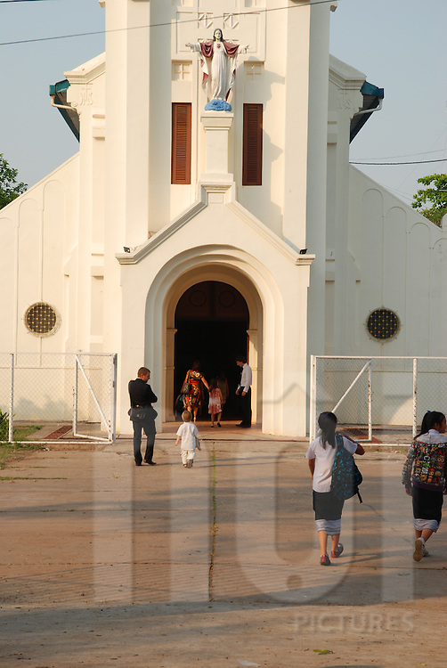 Frontage of a catholic church in Vientiane, Laos, Asia. worshipers enter to assist the mass