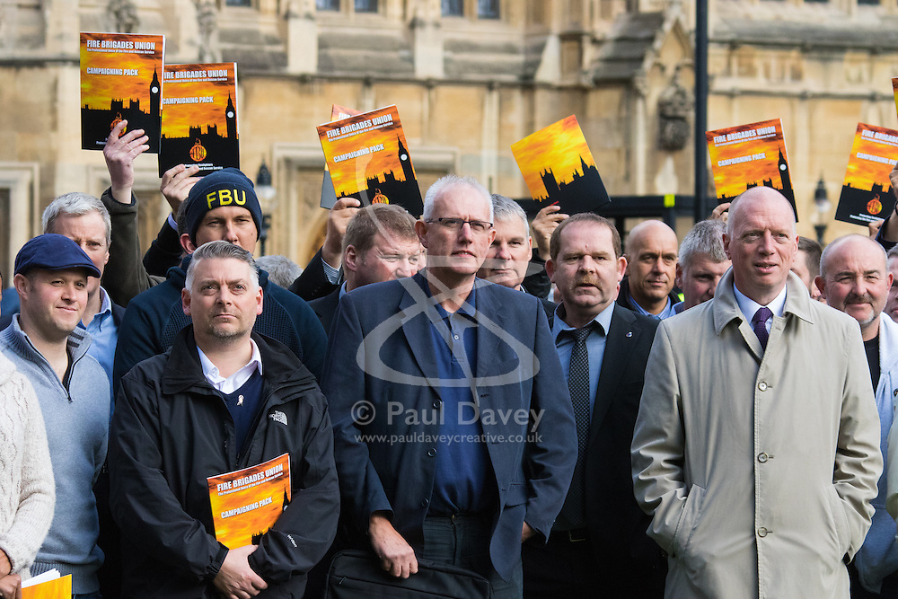 Westminster, London, October 14th 2015. Members of the FBU gather outside Parliament as they prepare to lobby MPs over cuts, the Trade Union Bill and the possibility of their service falling under the control of Police and Crime Commissioners. PICTURED: FBU Secretary General, second from right, poses with firefighters outside Parliament.