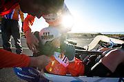 Christien Veelenturf wordt in de fiets geholpen tijdens een testochtend voorafgaand aan de recordraces de VeloX IV. Het Human Power Team Delft en Amsterdam (HPT), dat bestaat uit studenten van de TU Delft en de VU Amsterdam, is in Amerika om te proberen het record snelfietsen te verbreken. Momenteel zijn zij recordhouder, in 2013 reed Sebastiaan Bowier 133,78 km/h in de VeloX3. In Battle Mountain (Nevada) wordt ieder jaar de World Human Powered Speed Challenge gehouden. Tijdens deze wedstrijd wordt geprobeerd zo hard mogelijk te fietsen op pure menskracht. Ze halen snelheden tot 133 km/h. De deelnemers bestaan zowel uit teams van universiteiten als uit hobbyisten. Met de gestroomlijnde fietsen willen ze laten zien wat mogelijk is met menskracht. De speciale ligfietsen kunnen gezien worden als de Formule 1 van het fietsen. De kennis die wordt opgedaan wordt ook gebruikt om duurzaam vervoer verder te ontwikkelen.<br /> <br /> The HPT tests the VeloX4 speed bike. The Human Power Team Delft and Amsterdam, a team by students of the TU Delft and the VU Amsterdam, is in America to set a new  world record speed cycling. I 2013 the team broke the record, Sebastiaan Bowier rode 133,78 km/h (83,13 mph) with the VeloX3. In Battle Mountain (Nevada) each year the World Human Powered Speed ??Challenge is held. During this race they try to ride on pure manpower as hard as possible. Speeds up to 133 km/h are reached. The participants consist of both teams from universities and from hobbyists. With the sleek bikes they want to show what is possible with human power. The special recumbent bicycles can be seen as the Formula 1 of the bicycle. The knowledge gained is also used to develop sustainable transport.