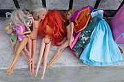 The discarded possessions of a young girl, part of a winters decluttering, consists of Barbie Dolls and her clothes, which are lined-up on a wall outside a residential home in Herne Hill, south London, on 23rd January 2021, in London, England.