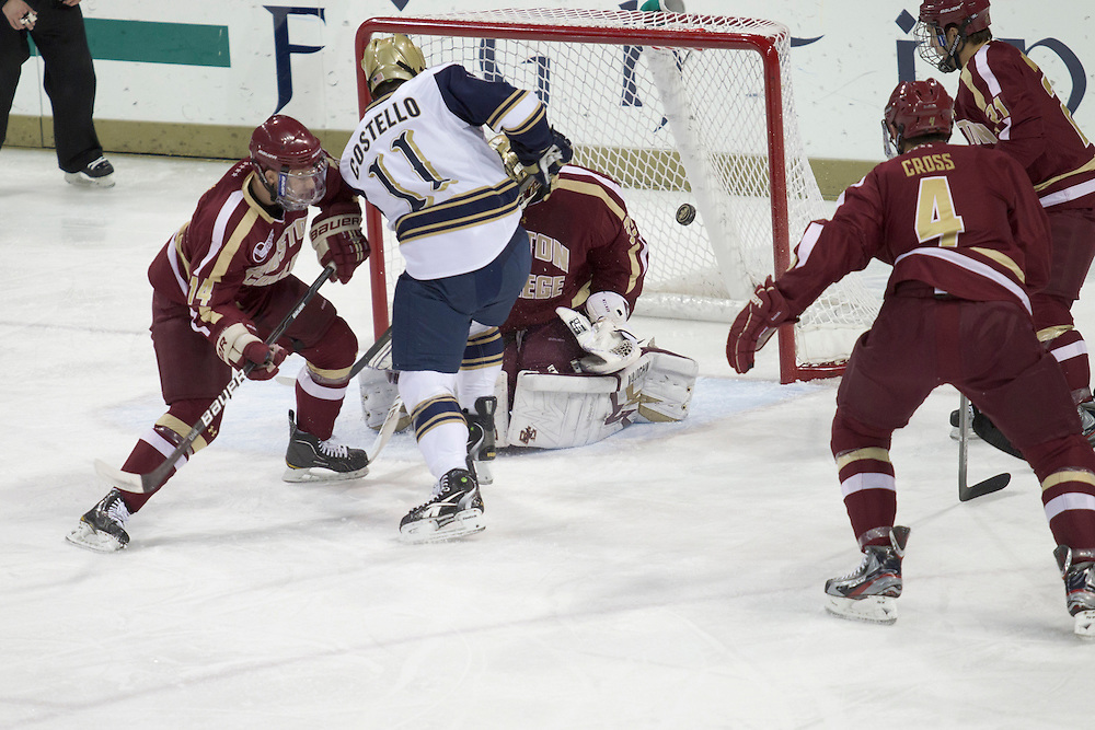 Notre Dame left wing Jeff Costello (#11) shoots the puck as Boston College forward Brooks Dyroff (#14) defends in action during NCAA hockey game between Notre Dame and Boston College.  The Notre Dame Fighting Irish defeated the Boston College Eagles 3-2 in game at the Compton Family Ice Arena in South Bend, Indiana.