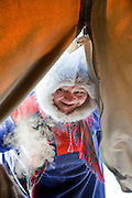 A Sami woman entering a lavvu, traditional temporary tent, in Karasjok, Finnmark region, northern Norway