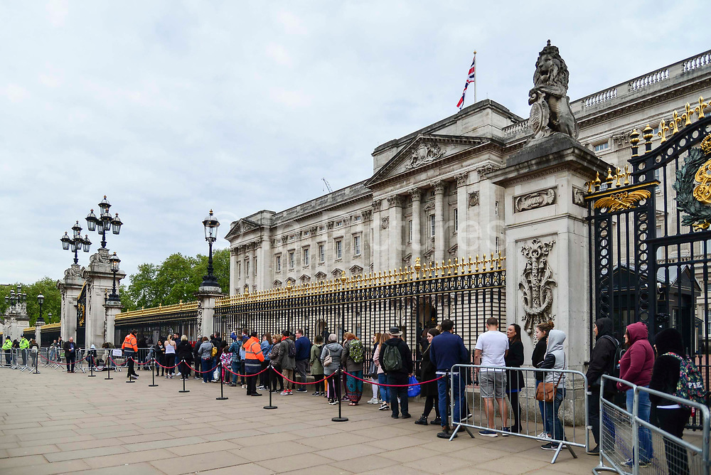 Members of the public queue to  photograph the official notice of the birth of a baby boy to the Duke and Duchess of Sussex outside Buckingham Palace on May 6, 2019 in London,England, United Kingdom. Meghan, Duchess of Sussex gave birth to a baby boy weighing 7lbs 3oz at 05:26 BST.