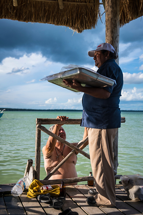 Bacalar, Mexico - June 2, 2021: A conversation at Bacalar Lagoon on the public dock at the end of Calle 36. Bacalar is located several miles from the border with Belize.