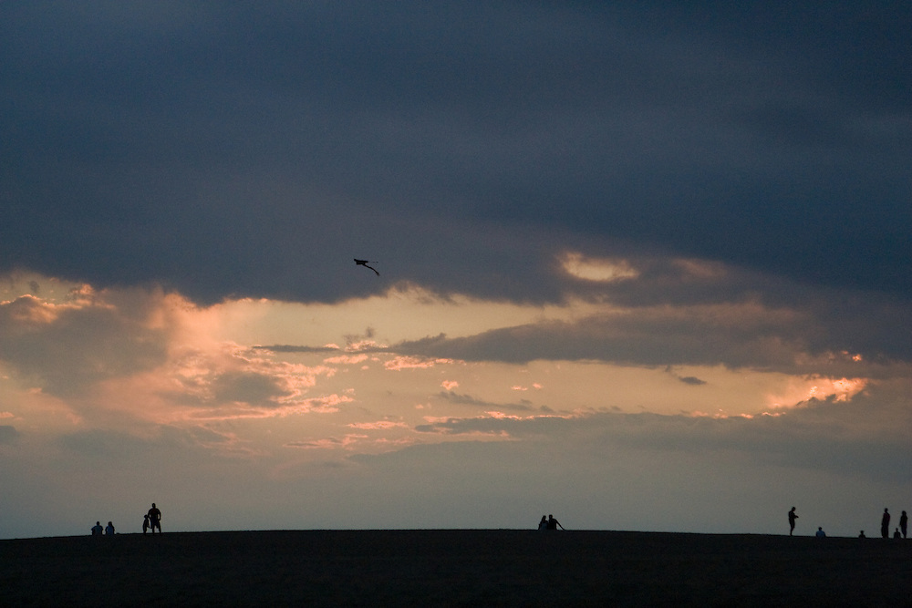 Families fly kites with their children as daylight recedes; Jockey's Ridge National State Park, North Carolina.