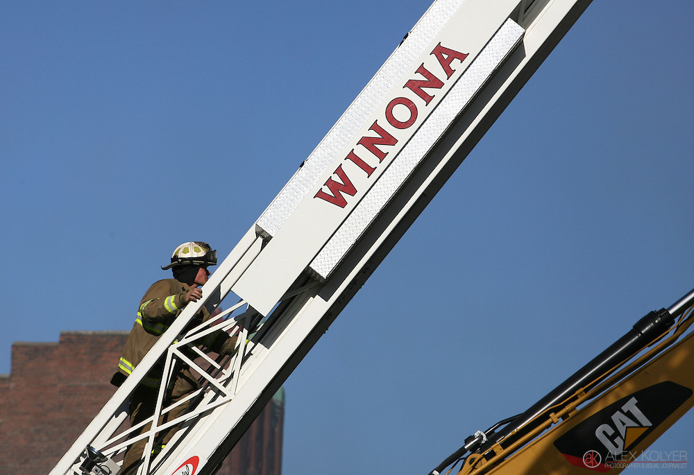 climb9/13/13--Winona<br /> A firefighter climbs an aerial ladder at the scene of a fire that destroyed three buildings in downtown Winona, Minn., Friday morning, Sept. 13, 2013. (Photo for MPR News by Alex Kolyer)
