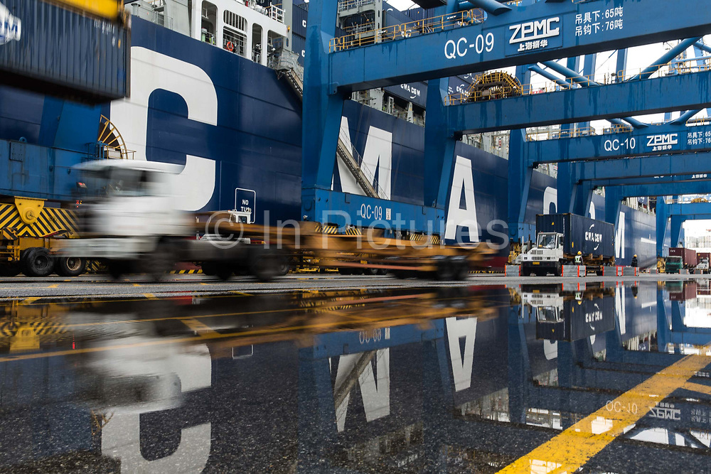 Trucks carrying containers wait to unload onto CMA CGM SAs Benjamin Franklin container ship while the ship is docked at the Guangzhou Nansha Container Port in Guangzhou, China, on Monday, Feb. 1, 2016. The Benjamin Franklin is the largest container ship ever to have docked at a U.S. port.