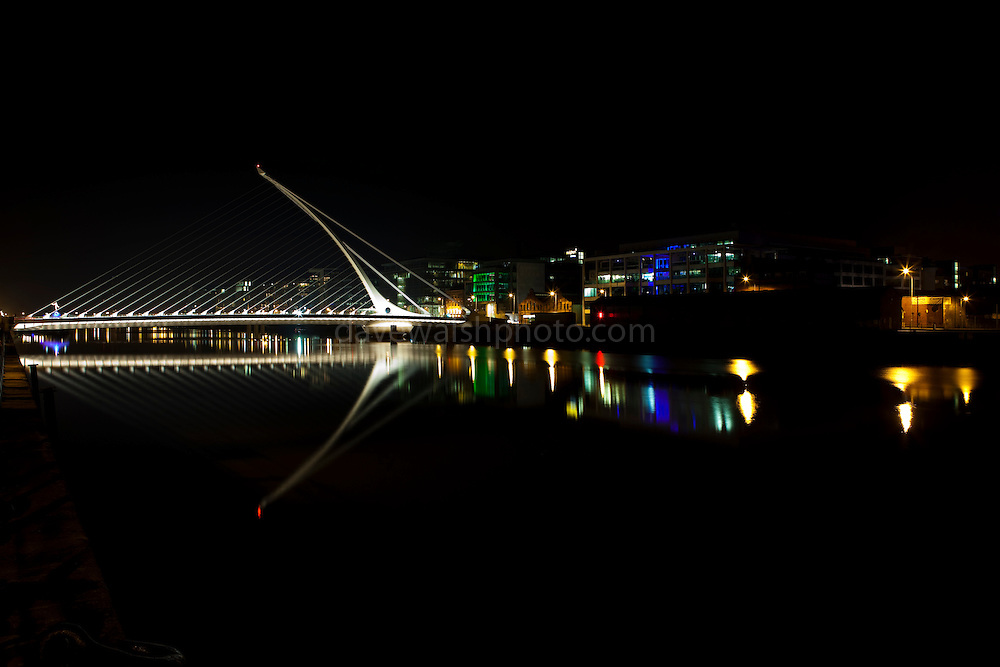 Samuel Beckett Bridge over the Liffey River at night with reflection, in Dublin Ireland. Constructed by Graham Hollandia Joint Venture, and designed by Spanish architect Santiago Calatrava. The bridge is 120 metres long and 48 metres high and weighs 5,700 tonnes.