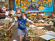 """12 JUNE 2020 - MINNEAPOLIS, MINNESOTA: A girl walks back to her mother after leading flowers at the impromptu memorial for George Floyd at the corner of 38th Street and Chicago Ave. in Minneapolis. The intersection is informally known as """"George Floyd Square"""" and is considered a """"police free zone."""" There are memorials to honor Black people killed by police and people providing free food at the intersection. Floyd, an unarmed Black man, was killed by Minneapolis police on May 25 when an officer kneeled on his neck for 8 minutes and 46 seconds. Floyd's death sparked weeks of ongoing protests and uprisings against police violence around the world.          PHOTO BY JACK KURTZ"""