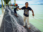 23 AUGUST 2018 - TELUK BAHANG, PENANG, MALAYSIA: A crewman on a commercial fishing trawler in Teluk Bahang, on the island of Penang, sorts lines used to drag nets. Fishermen on Penang, an island off the west coast of mainland Malaysia, are being pressured by the island's resort development and reduce catches in the waters off Malaysia.     PHOTO BY JACK KURTZ