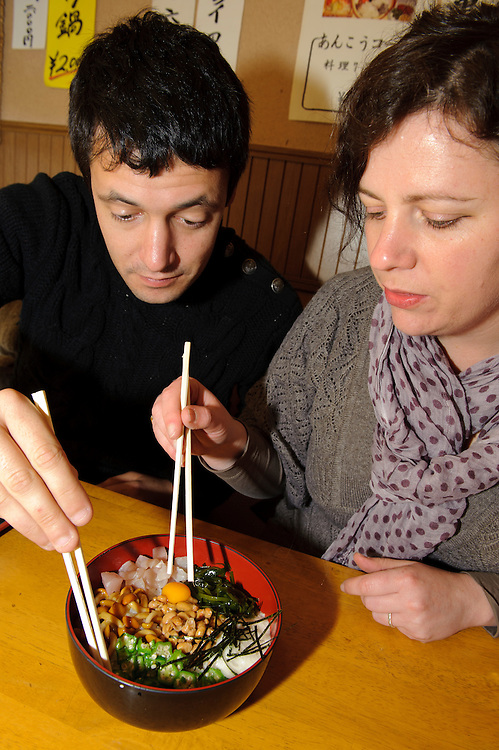 Jess and Anthony try a dish containing natto and various slimy ingredients, Natto restaurant, Mito, Ibaragi Pref, Japan, April 17, 2010.