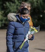 13th, March, 2021. Cheltenham. A member of the public with a bouquet of flowers in memory of Sarah Everard.