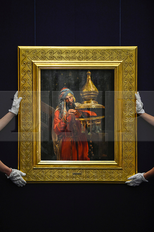 """© Licensed to London News Pictures. 11/10/2019. LONDON, UK. Technicians present """"Lighting the Lamp"""", by Antonio Fabrés Y Costa, (Est GBP100-150k).  Preview of works from the Najd Collection of orientalist paintings at Sotheby's in New Bond Street, which record daily life in the historic Arab, Ottoman and Islamic worlds  All 155 paintings are on public view 11- 15 October, with 40 works to be auctioned on 22 October.  Photo credit: Stephen Chung/LNP"""