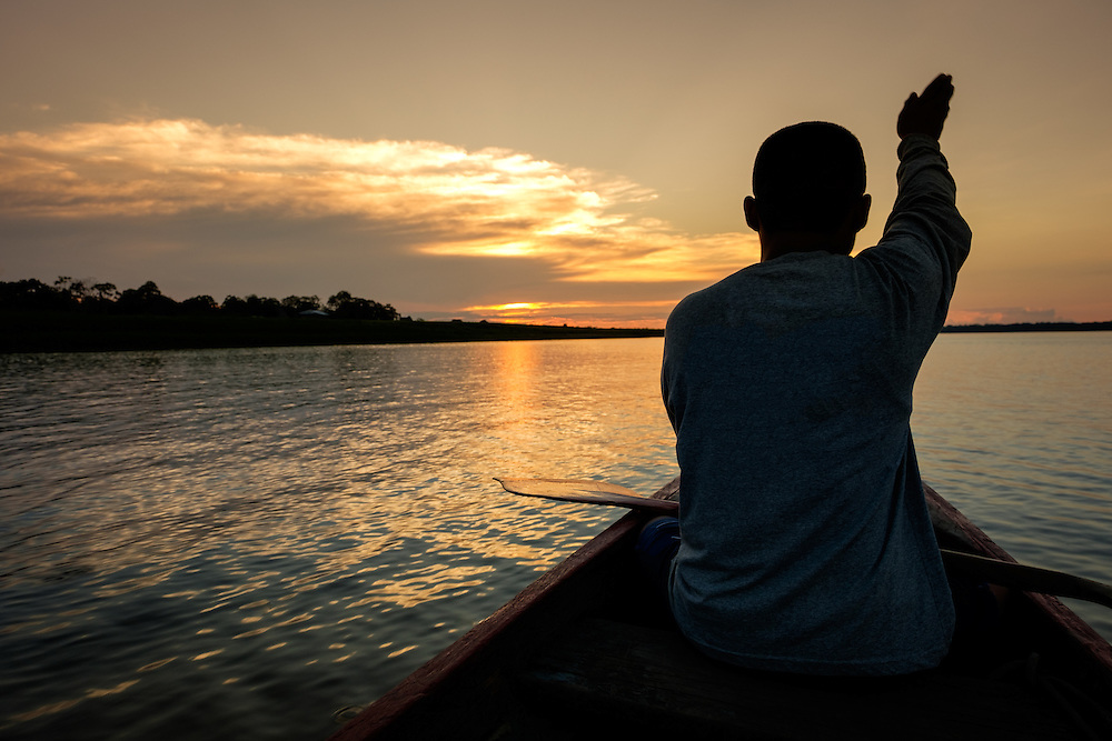 LORETO, PERU - CIRCA OCTOBER 2015:  Local guide marking directions during sunset in the Ucayali river in the Peruvian Amazon.