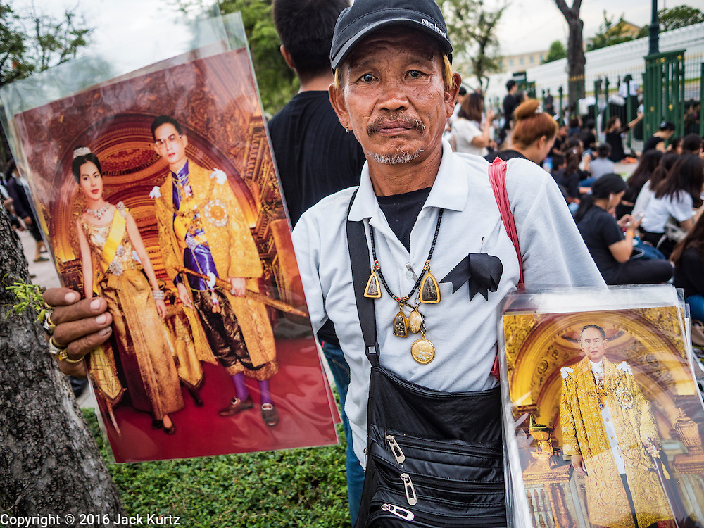 17 OCTOBER 2016 - BANGKOK, THAILAND:  A man walks through the crowd selling portraits of Bhumibol Adulyadej, the late King of Thailand, at Sanam Luang in central Bangkok. Thai King Bhumibol Adulyadej died Oct. 13, 2016. He was 88. His death comes after a period of failing health. Bhumibol Adulyadej, was born in Cambridge, MA, on 5 December 1927. He was the ninth monarch of Thailand from the Chakri Dynasty and is also known as Rama IX. He became King on June 9, 1946 and served as King of Thailand for 70 years, 126 days. He was, at the time of his death, the world's longest-serving head of state and the longest-reigning monarch in Thai history.       PHOTO BY JACK KURTZ