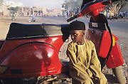 Muslim Husa boy with vespa motorbike near the central mosque during the Kano Durbar Fantasia..The Durbar Fantasia, is the moment where The Husa residents of Kano wear traditional dress, their local leaders and chiefs mount horses, and together with their militias display allegiance and homage to their leader, the Emir of Kano. This takes place after Ramadan. The Emir is Kano's State official political and economic feudal leader, everyone seeks to be in his pleasure, otherwise they reap the consequences..Kano is the largest Muslim Husa city, under the feudal, political and economic rule of the Emir. Kano and the other eleven northern states are under Islamic Sharia Law which is enforced by official state apparatus including military and police, Islamic schools and education, plus various volunteer Militia groups supported financially and politically by the Emir and other business and political bodies. 70% of the population live below the poverty line. Kano, Kano State, Northern Nigeria, Africa