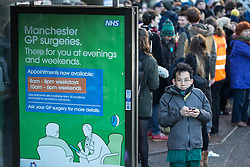 © Licensed to London News Pictures . 12/01/2016 . Manchester , UK . A Junior Doctor standing beside a poster at a bus stop advertising late night weekday and weekend GP services , adjacent to the picket . Junior doctors walk out to a picket outside the Manchester Royal Infirmary in England as the first of three planned strikes over pay and working conditions starts this morning (12th January 2016) at 8am . Photo credit : Joel Goodman/LNP