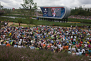 A crowded grassy area of spectators watch the rowing race on large TV screen in the Olympic Park during the London 2012 Olympics. The planting of 4,000 trees, 300,000 wetland plants and more than 150,000 perennial plants plus nectar-rich wildflower make for a colourful setting for the Games. This land was transformed to become a 2.5 Sq Km sporting complex, once industrial businesses and now the venue of eight venues including the main arena, Aquatics Centre and Velodrome plus the athletes' Olympic Village. After the Olympics, the park is to be known as Queen Elizabeth Olympic Park.
