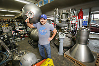 Norton Sales President and owner Carlos Guzman holds a titanium fuel tank used  in the LR-87 rocket engine behind him in North Hollywood Jan. 8, 2018 Photo by David Sprague