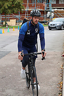 AFC Wimbledon fitness coach Jason Moriarty arriving on a bike during the EFL Sky Bet League 1 match between AFC Wimbledon and Rochdale at the Cherry Red Records Stadium, Kingston, England on 5 October 2019.