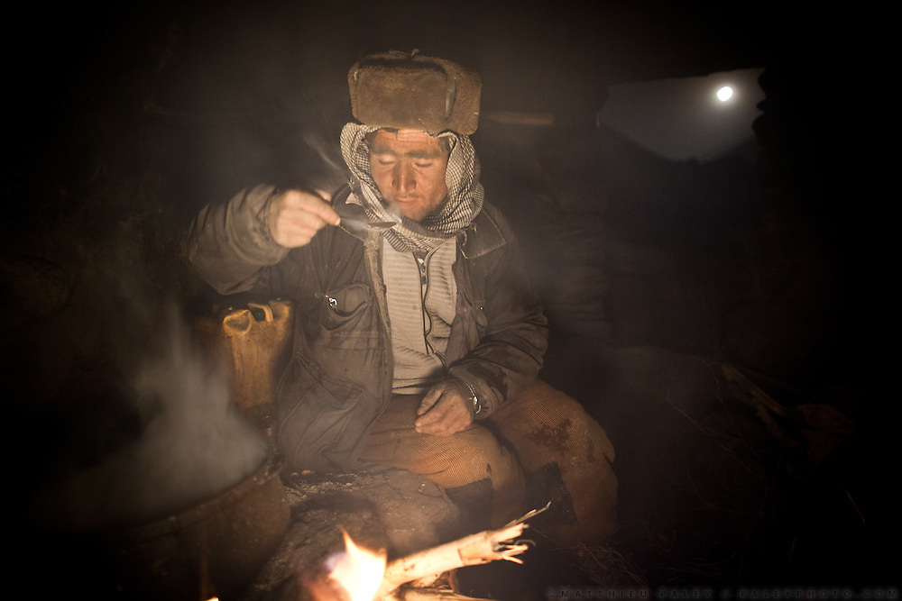 A Wakhi man cooks tea while a full moon rises outside. Inside Zang Kuk shepherd house. Full moon rising..Going back down to Sarhad village with a yak caravan led by 2 Wakhi traders: Shur Ali and Roz Ali...Trekking down the Wakhan frozen river, the only way down to leave the high altitude Little Pamir plateau, home of the Afghan Kyrgyz community.