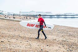 © Licensed to London News Pictures. 26/09/2020. Brighton, UK. Brighton And Hove Surf Life Saving Club member KAI RICHENS returns from a surfing session in Brighton and Hove. Only a handful of people can be seen on the beach as colder weather is hitting the seaside resort. Photo credit: Hugo Michiels/LNP