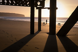 © Licensed to London News Pictures. 07/04/2016. Sandown, UK. A man walking his dogs near the pillars of Sandown Pier in Sandown Bay on the Isle of Wight this morning, Thursday 7th April 2016. Photo credit : Rob Arnold/LNP