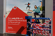 Exuberant youth taking selfies in an ad for Vodafone with a taped up construction cage in central London. The advert shows us the vitality and lust for life when using one of this communications brand's smartphones. A man holds up a phone to film a friend who is mid-air on a skateboard - the joy and pleasure of using the device shown to us, the consumer. The ad tells us of the latest deal that ends at the end of the month. At the bottom are the stripes of hazard tape that stops passers-by from injuring themselves.