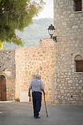 Rear view of senior man with walking stick, Avgonyma, Chios, Greece