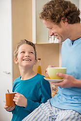 Smiling father and son with cups in kitchen
