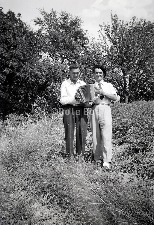 two friends posing with accordion 1950s countryside