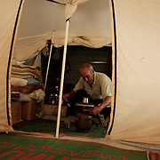 August 08, 2013 - Zaatari, Jordan: Abed Almonem, a 65 year old syrian refugee from Daraa city, prepares a coffee in his tent at Zaatari refugee camp, in northern Jordan. Mr. Almonem, a farmer by trade, fled the fighting in Syria one year ago, when his house and his cattle got destroyed by regime forces. Like many other refugees in Zaatari, Mr. Almonem lost some family members during the attack to his village, leaving behind all his worldly possessions. He lives now at the camps with his wife and two children, and depends uniquely on basic aid provided by international Non-Governmental Organisations. Despite the harsh conditions at Zaatari, Mr. Almonem sees no reason to go back to Syria till the war in over. Zaatari camp, home to more than 120,000 people who in the past year have fled the conflict in Syria, become the fourth largest city in Jordan and the world's second largest refugee camp behind Dadaab in eastern Kenya. Most of its residents came from Daraa, a city about 30Km away in Syria, rich with businessmen thanks to a long history of cross-border trade with Jordan. (Paulo Nunes dos Santos/Al Jazeera)