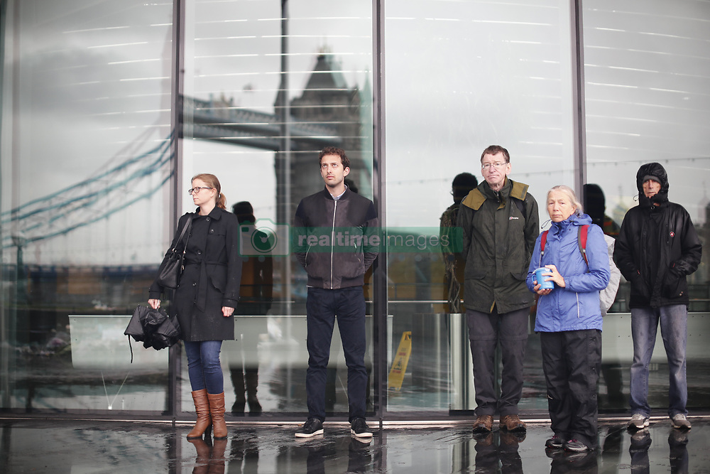June 6, 2017 - London, London, UK - London, UK.         A minutes silence is held outside City Hall, next to a flower tribute in central London for those who lost their life in a terrorist attack on Saturday evening. Three men attacked members of the public  after a white van rammed pedestrians on London Bridge. Ten people including the three suspected attackers were killed and 48 injured in the attack. (Credit Image: © Tolga Akmen/London News Pictures via ZUMA Wire)