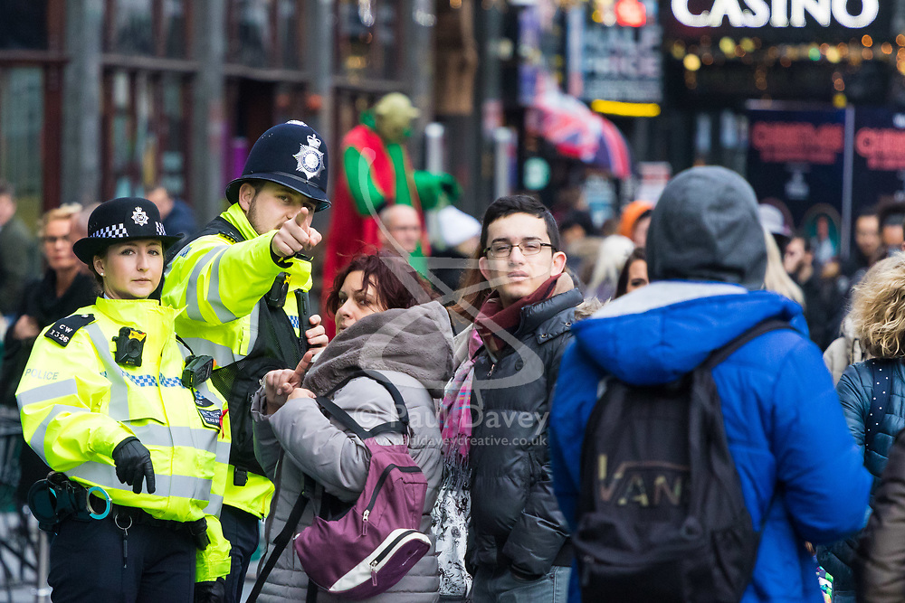 London, December 31 2017. Police in high visibility jackets and numerous anti-terrorism and crowd control measures are in place in the capital ahead of the New Year's Eve fireworks and revelry in central London. PICTURED: Police officers in Leicester Square give directions to tourists. © SWNS