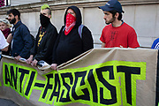 Demonstrators hold up a banner for the London Anti-Fascist Assembly wearing masks gather to oppose the Free Tommy Robinson demonstration, organised by anti-fascist groups including Stand up to Racism opposed to far right politics on 24th August 2019 in London, United Kingdom. Some 250 Stand Up To Racism and other anti-fascist groups took to the streets today in opposition to supporters of jailed 'Tommy Robinson' real name Stephen Yaxley-Lennon at Oxford Circus, who gathered outside the BBC.
